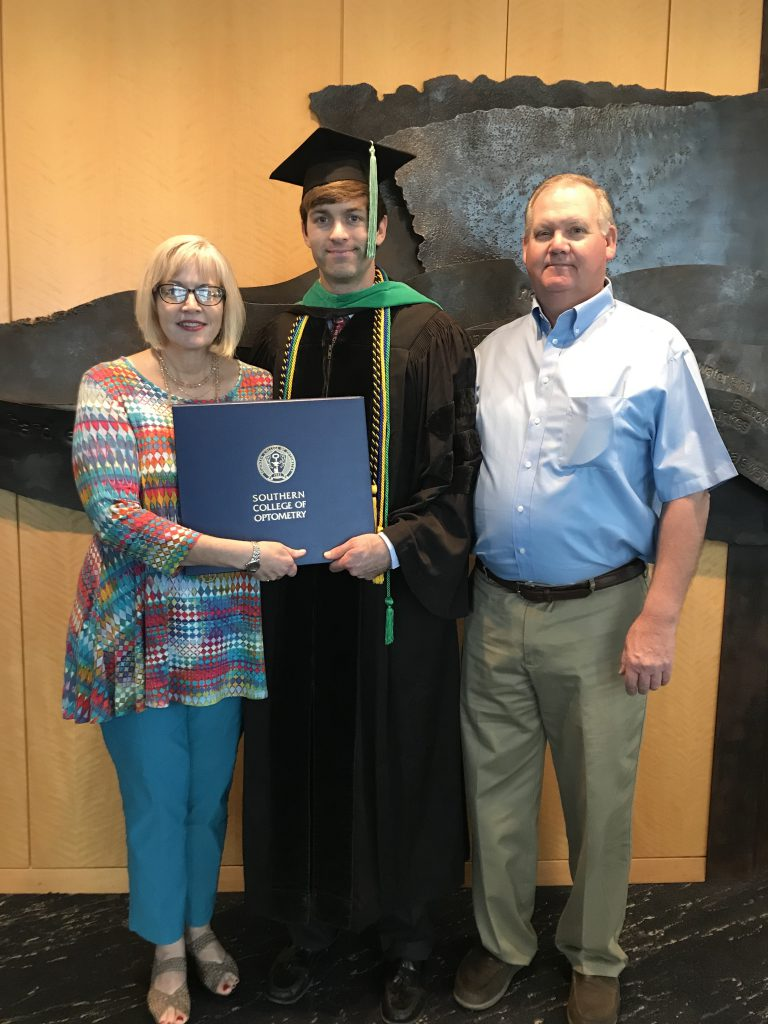 Slater poses for a photo with his mom and dad at graduation.