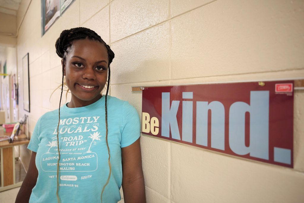 Monae poses by a sign in the Career Tech Center.