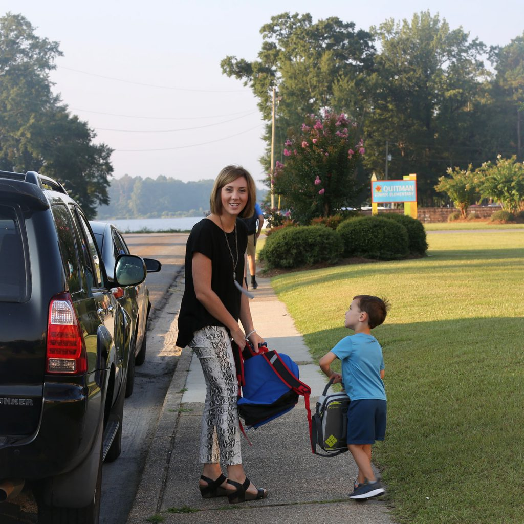 A QLE parent walks her son to school.