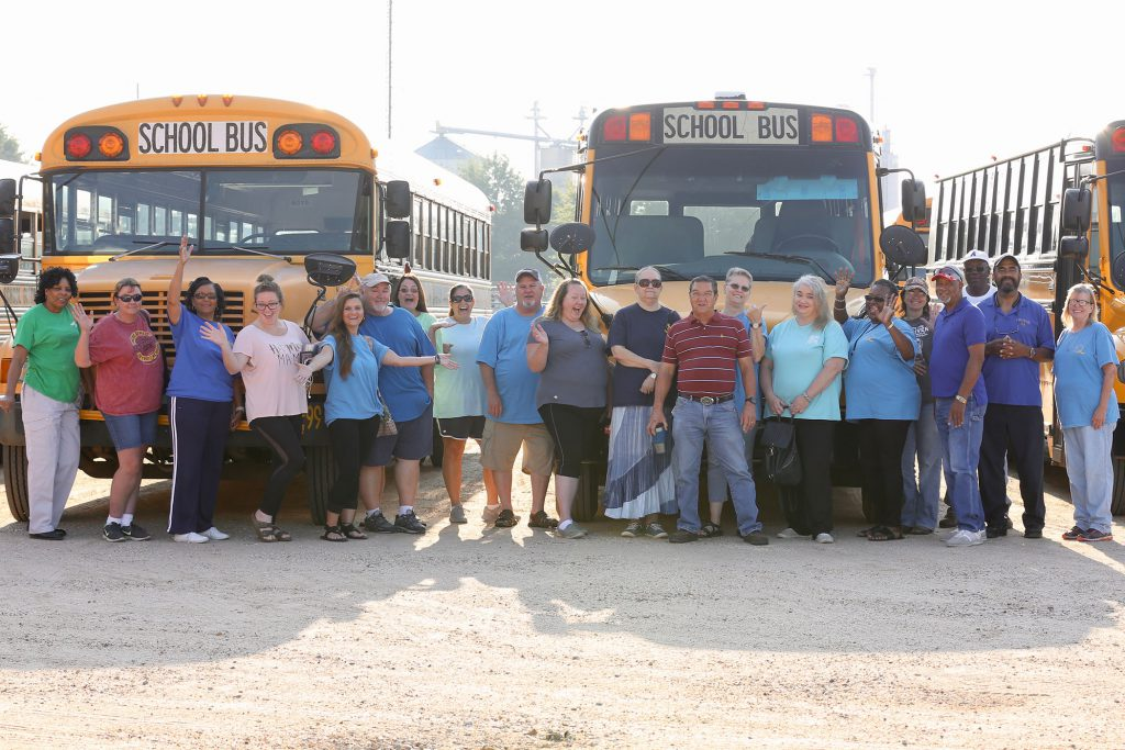 QSD Transportation Department poses beside their buses.