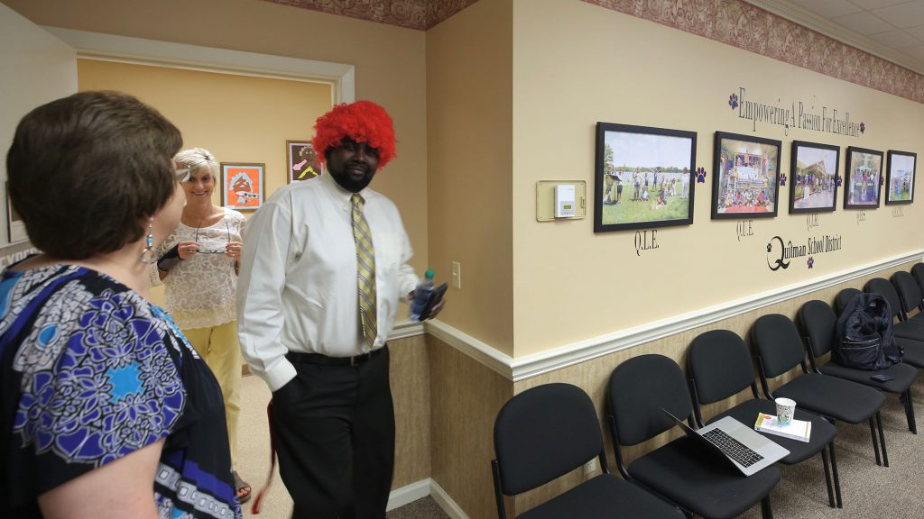 School leaders wear wigs to a meeting.