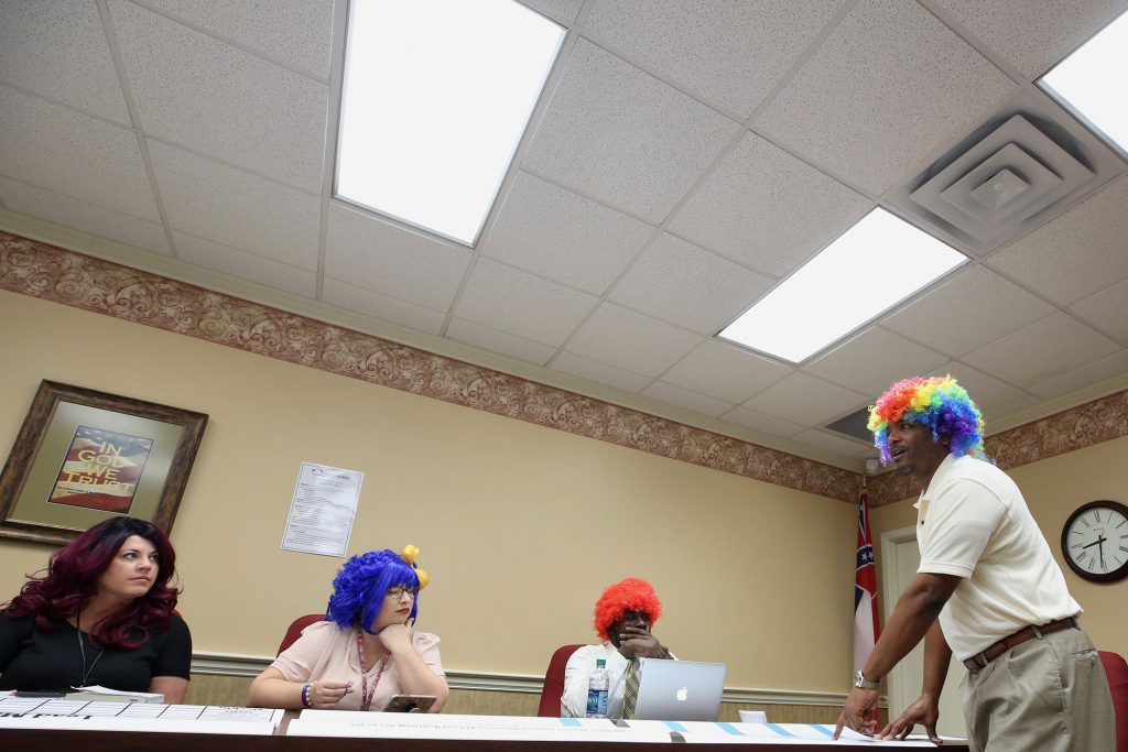 QSD leaders wear wigs to a meeting.