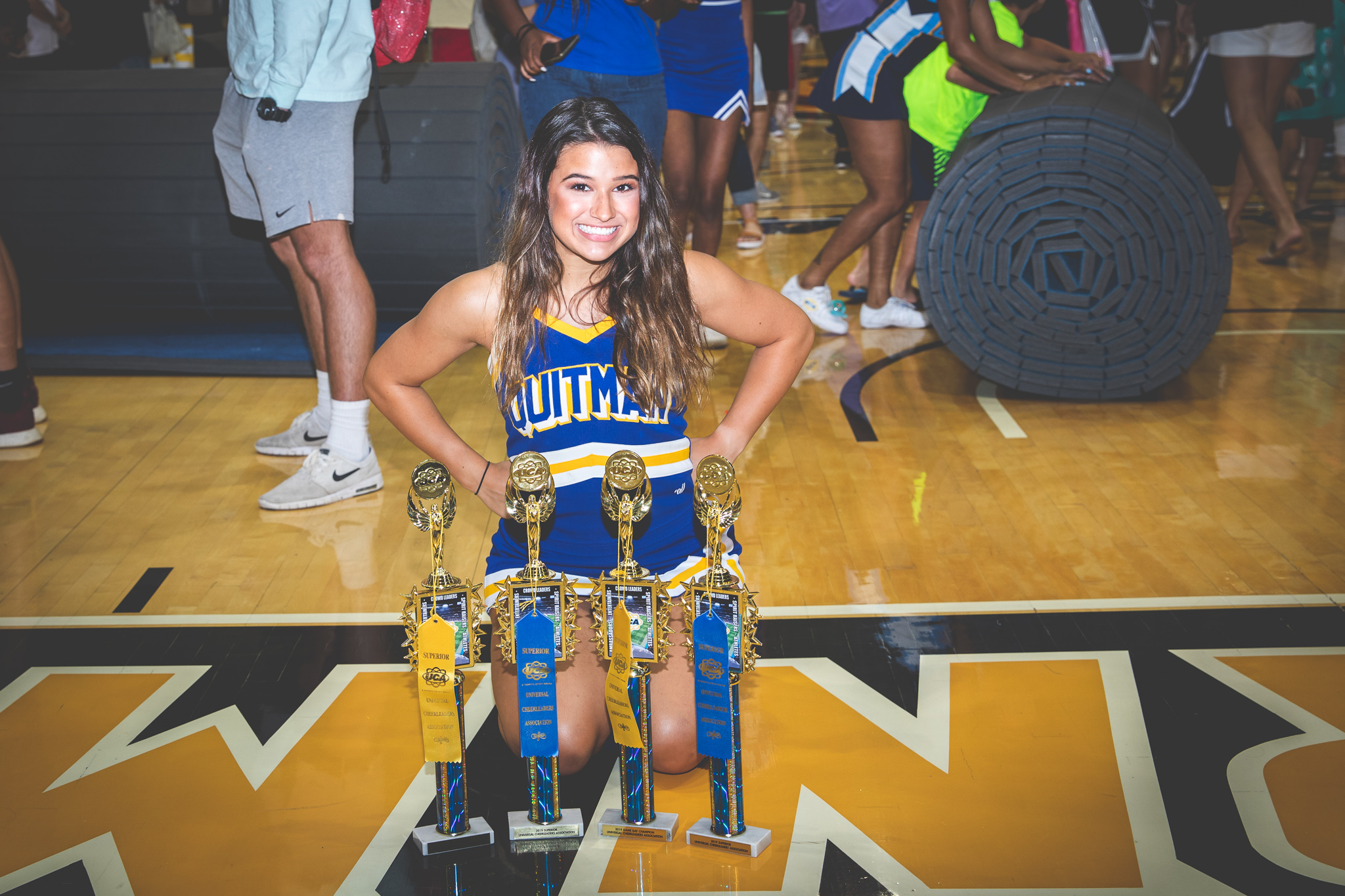 Erin poses behind trophies at cheer camp.