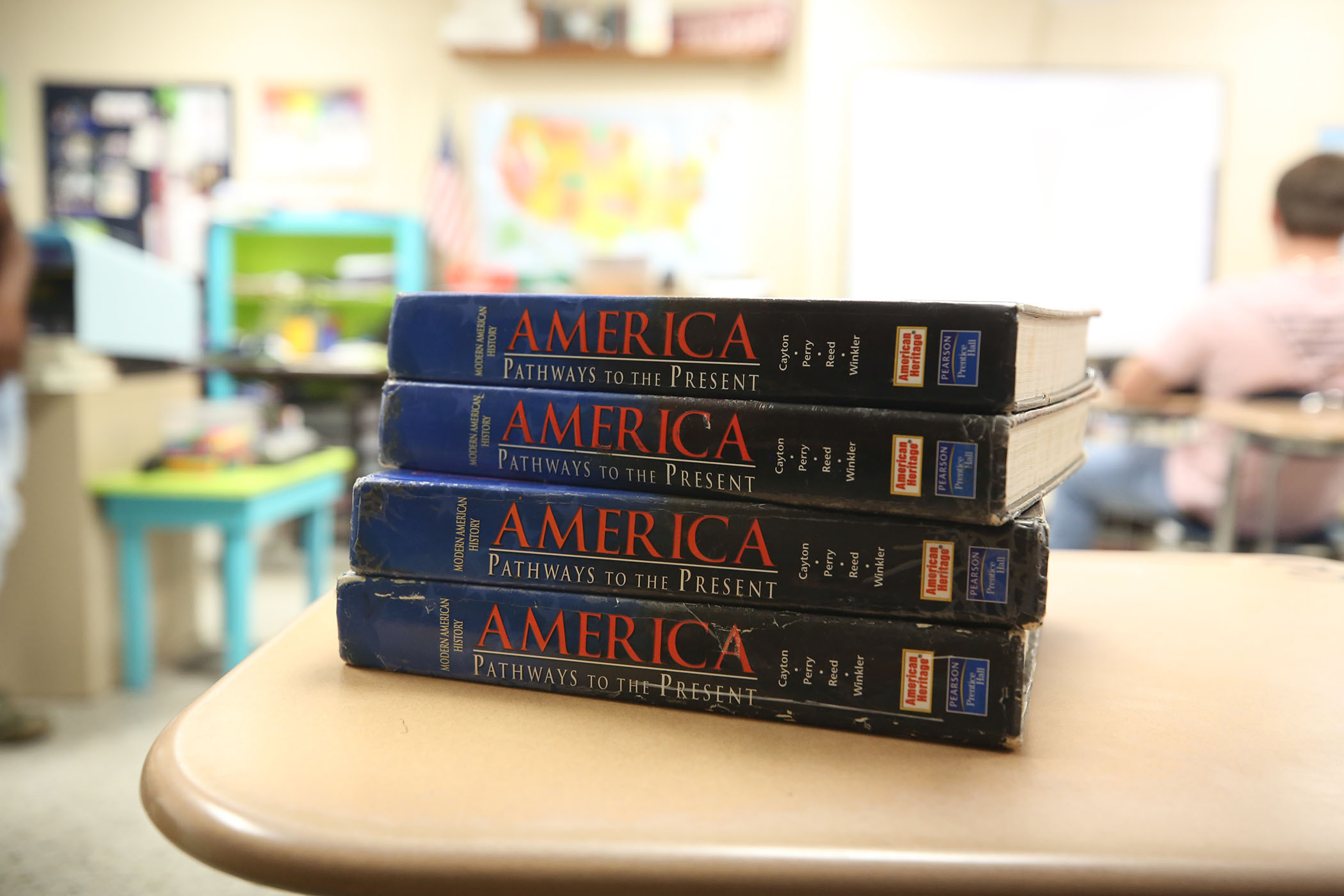 American history books are stacked on a desk in history class.