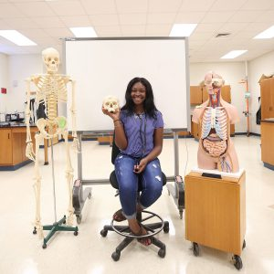 AA'Cahsha holds a skull in the chemistry lab.