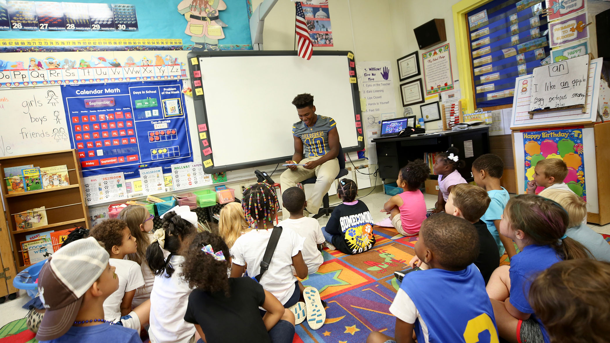Jamal reads to a class of kindergarteners at QLE.