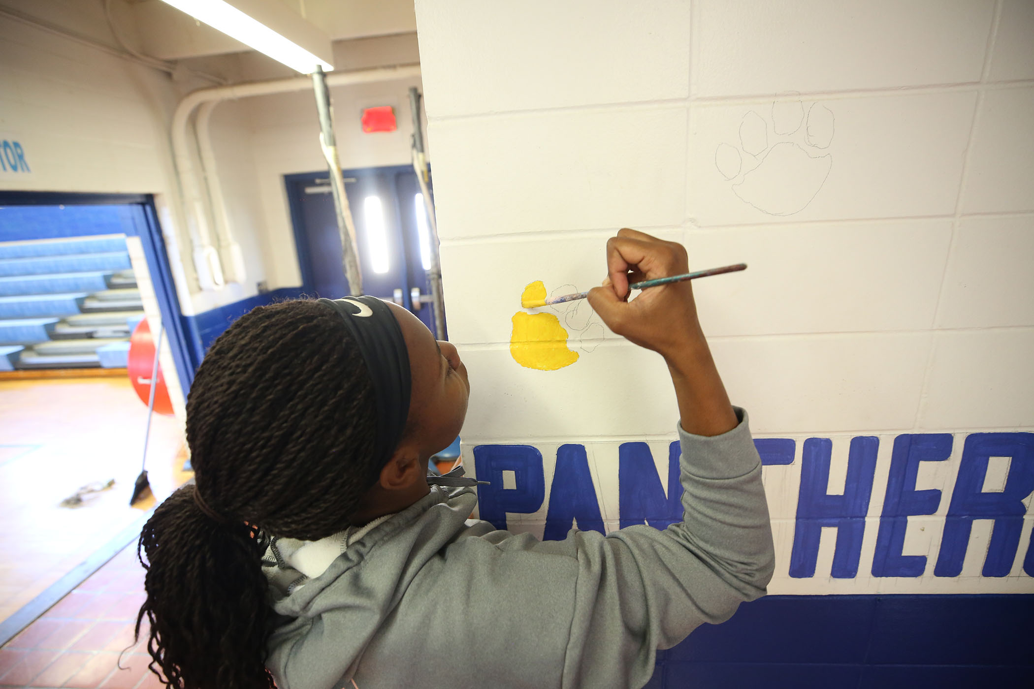 Panthers help paint their gym, affectionately called their House.