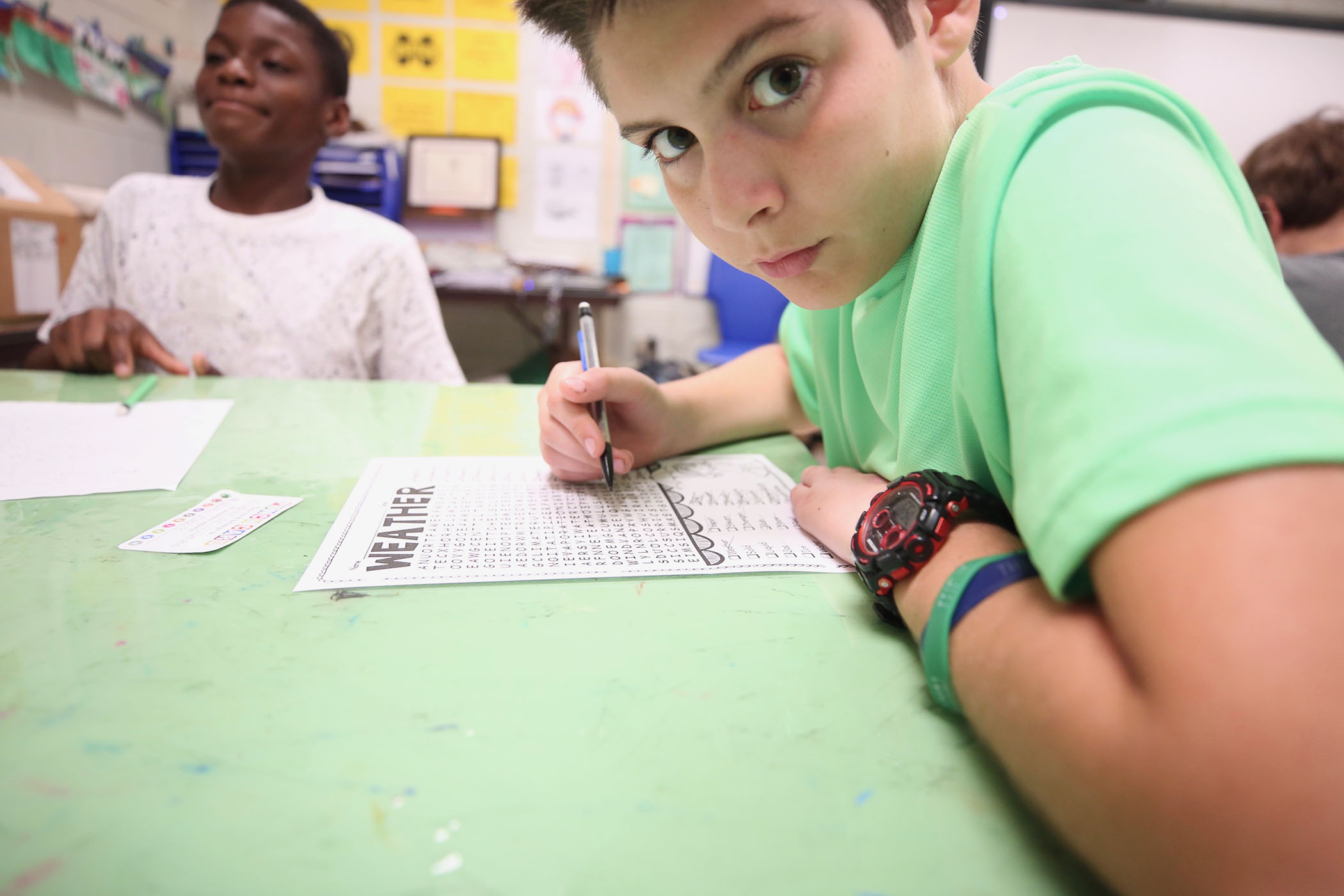 A student does bellringer work before art class at QJH.