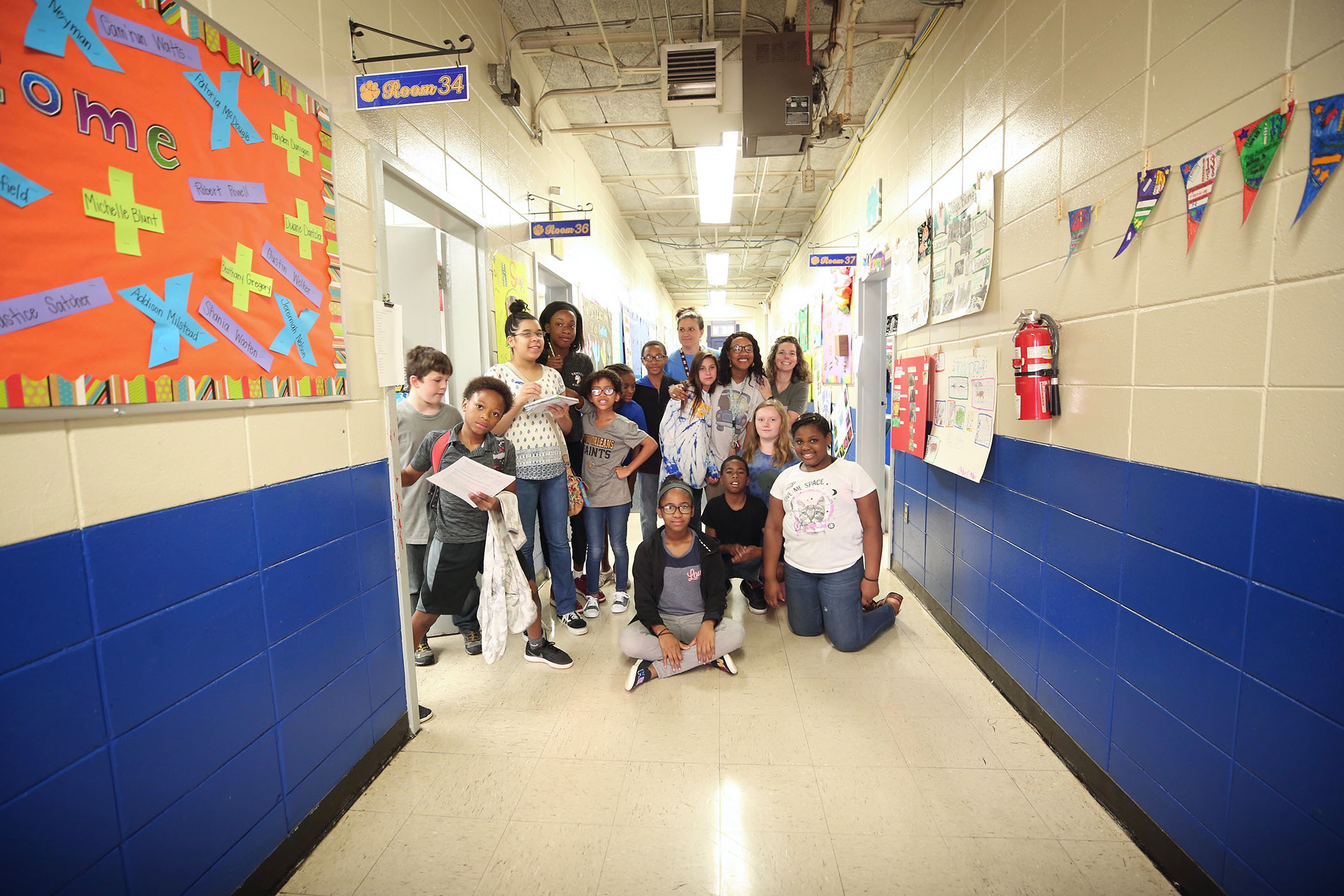 QUE students pose in the hallway with their teachers.