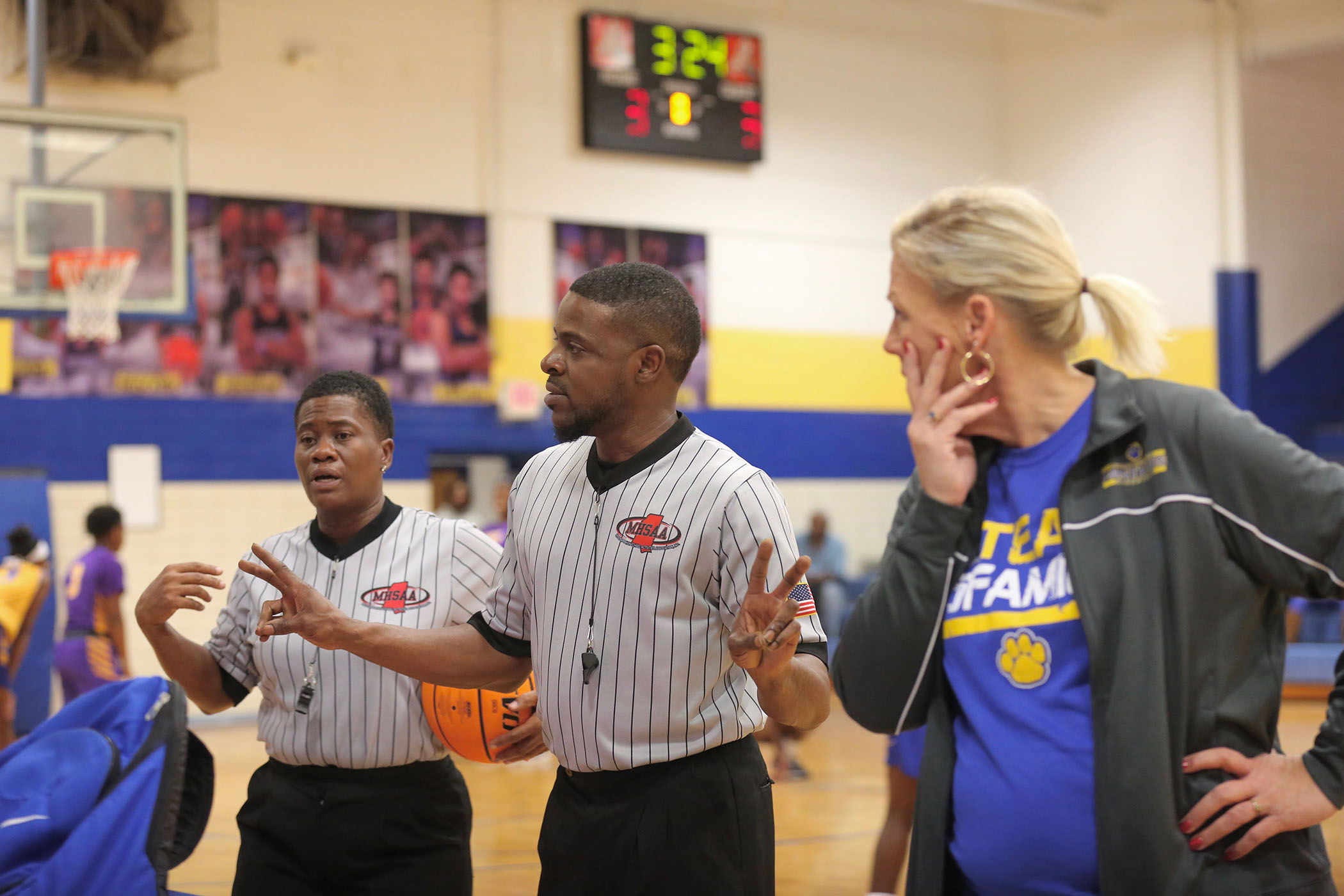 Coach Vance questions a call in a basketball game.