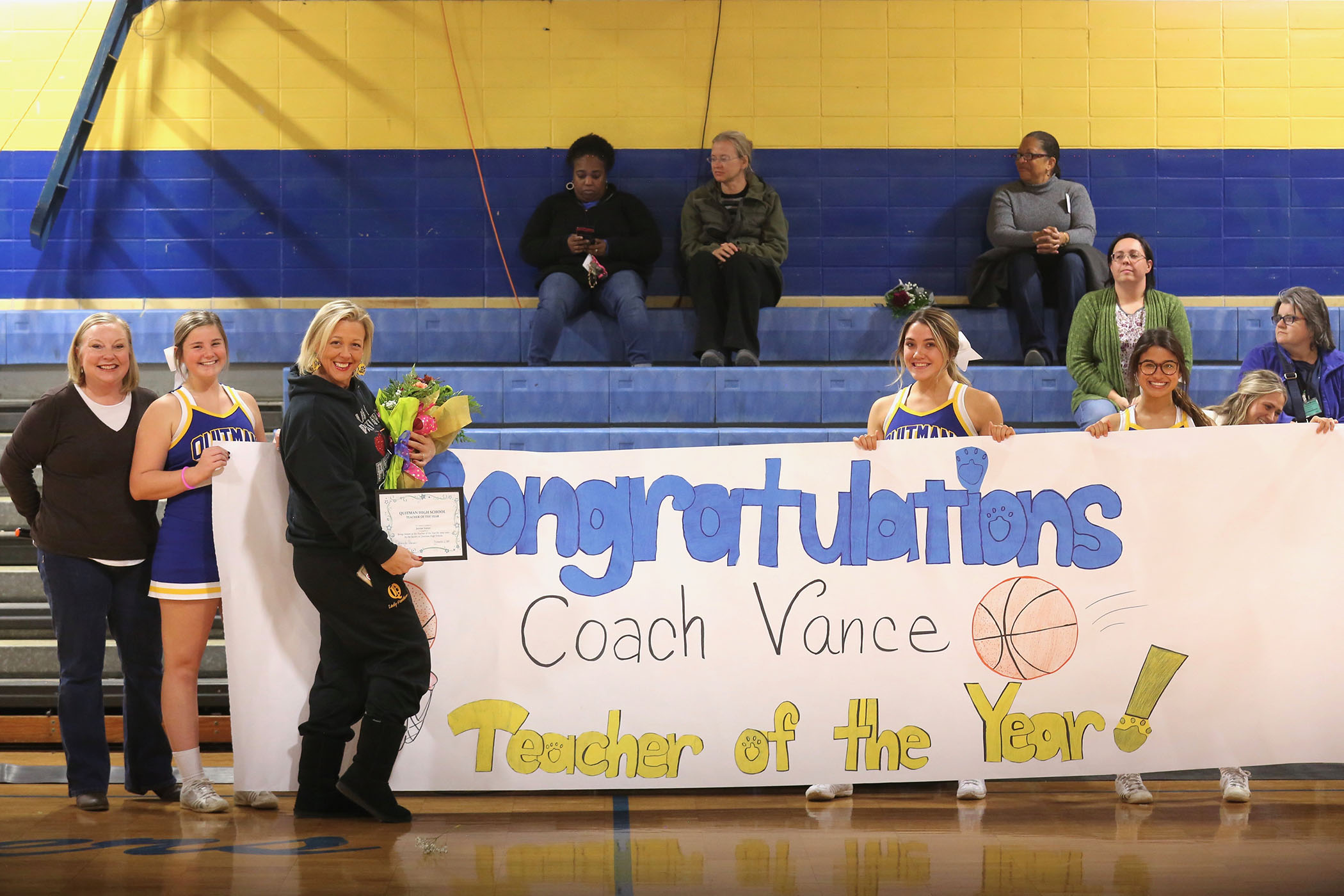 Coach Vances poses by her Teacher of the Year sign.
