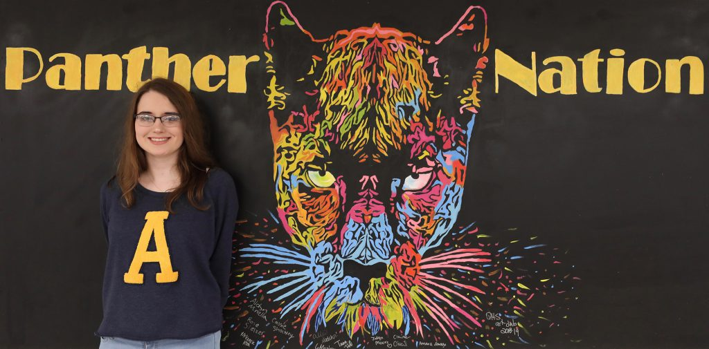Aldyn stands next to a mural she helped paint.