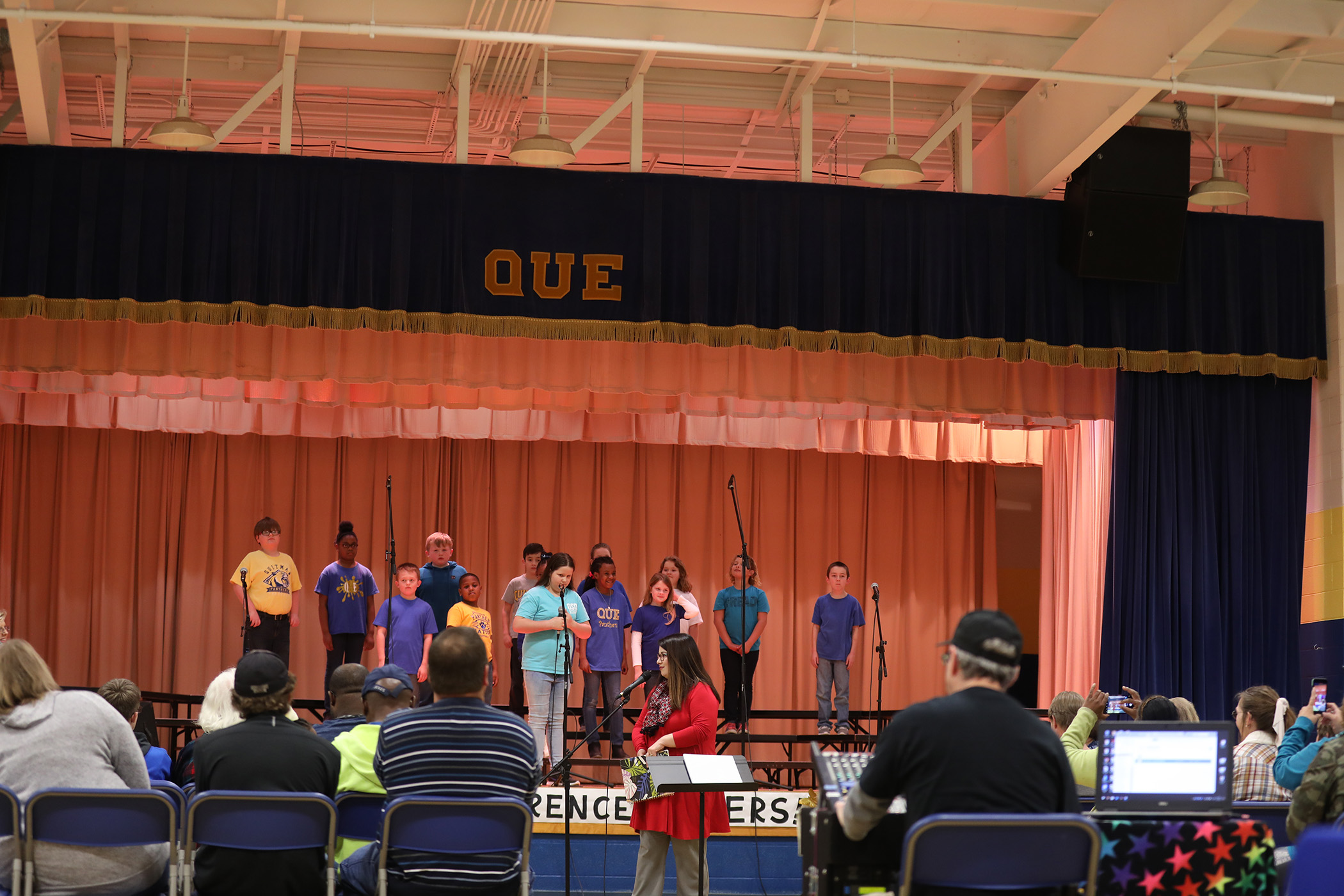 QUE singers celebrate at a PTO meeting.
