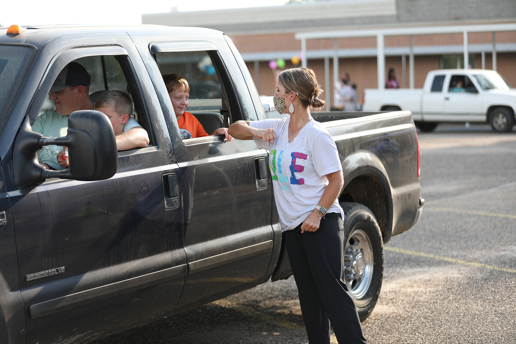 A QLE teacher greets a student at the QLE Back to School Parade.