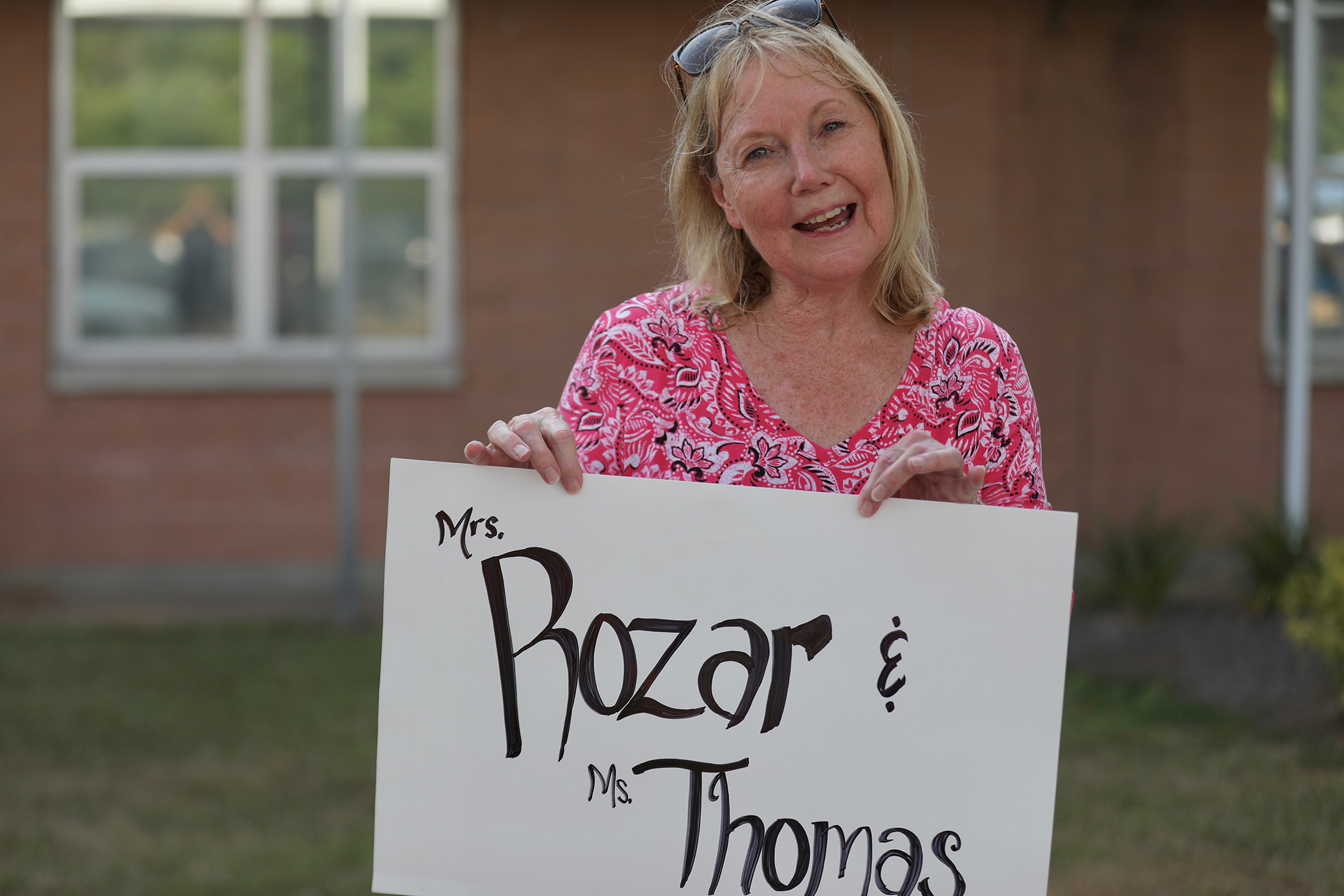 Mrs. Rozar holds a sign during the Back to School Pre-K Parade.
