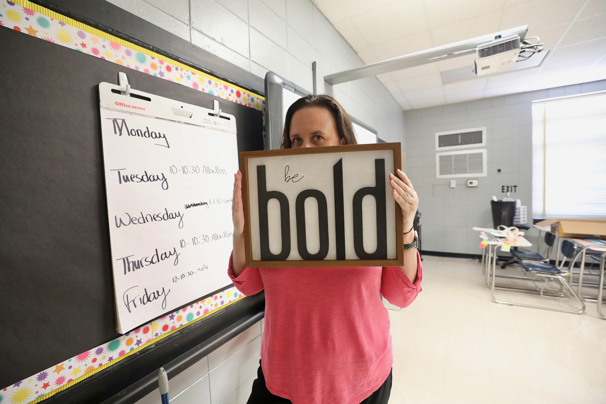This is a photo of a teacher holding a sign.